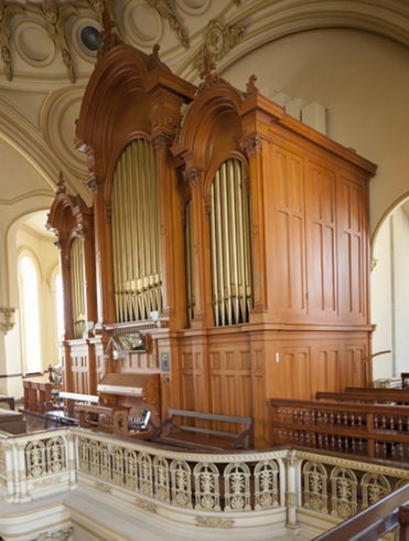 At the balcony: organ side view. Three carved wooden part with a higher central part. Vertical pipes. Front: keyboard and bench. In the foreground, worked railing.