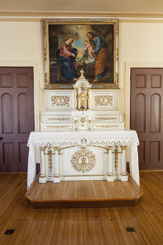 Centered between two doors. Sculpt white and gilded altar and altarpiece. A painting of the Holy Family. Front: Child jesus statuette. Crowned and gilded.