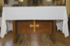 Rectangular wooden Altar table, light wooden Cross applied up front. Covered by a white tablecloth.