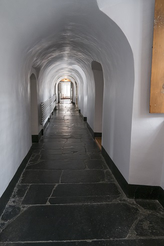 Corridor white vaulted. Large bright window at the bottom. Very thick walls. Doors on each side. Dark stone floor.