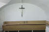 Long wooden container. White room with vaulted ceiling. Large crucifix in the center of the wall.