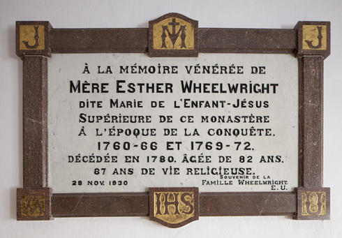 Commemorative plaque fixed of the wall. Tribute to mother Esther Wheelwright. Black letter text on white marble. Brown contour, with letters on  gilded backgrounds.