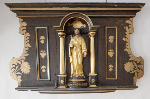 In a dark brown wood with gilded  ornaments alcove, between two small columns, a St-Joseph statue with golden clothes, scepter in his hand.