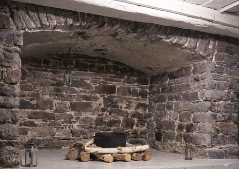 Large fireplace made of grey stones. A the center, wooden logs holding a large black iron-cast cauldron. Two lantern on both sides on the floor.