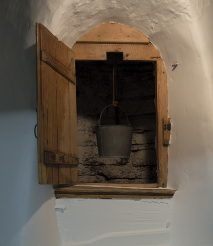 In a thick with wall, a small light wooden door is open. We see the stone wall of the well and a hanging bucket.